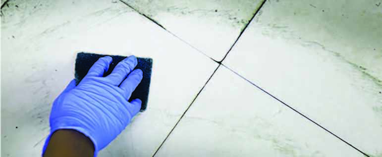 Hand of a cleaner wearing a glove cleaning bathroom floor with a scrubber