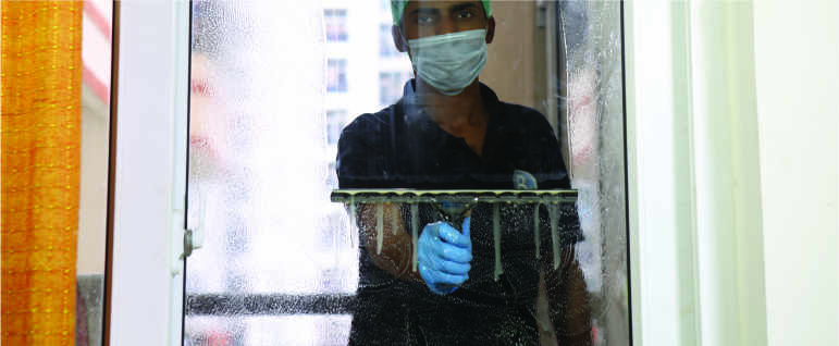 A cleaner wearing a sust mask and head cap cleaning the glass of a window using a squeegee